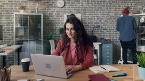 Просигнальте в промежутке времени молодой женщины используя деятельность ноутбука на проекте в офисе сток-видео