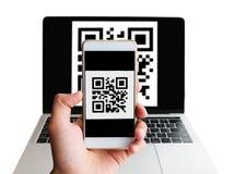 Просматривая ноутбук forn кода QR используя мобильный смартфон стоковое изображение rf
