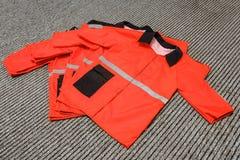Простая красная рабочая одежда штабелированная в куче стоковые изображения rf
