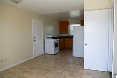 Простая кухня с рядом, шкафами, холодильником, плиточным полом стоковая фотография
