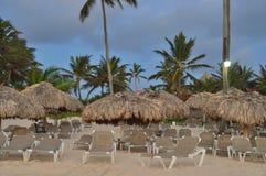Простирание пляжа на атлантическом побережье в вечере, зонтиках пляжа, sunbeds, пальмах, горящий загораться фонарика стоковое фото
