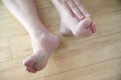 Простирания более старого человека для того чтобы касаться его пальцу ноги Стоковые Фото