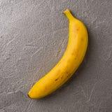 Простое изображение одиночного зрелого желтого банана на сером металлическом backg Стоковые Фотографии RF