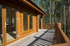 Просторная терраса деревянного дома в лесе с большим ветром Стоковые Изображения