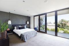 Просторный интерьер дизайнерской спальни хозяев в роскошной Австралии Стоковое фото RF