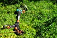 Простые моменты жизни, обычная работа в саде - человек уравновешивая траву со сверхмощным триммером в саде стоковая фотография