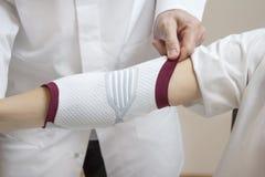Протезный хирург в белом пальто принимает стабилизатор на локте женщины стоковые изображения rf