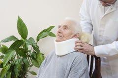 Протезный хирург кладет дальше белый протезный воротник очень старухи сидя на стуле стоковые фотографии rf