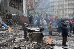 Протестующие горят огонь около баррикад после столкновений с полицией на разрушенной улице во время антипровительственного протест стоковая фотография