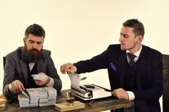 Противозаконная концепция дела Люди сидя на таблице с кучами денег и машинки Дело приниманнсяое за компанией противозаконное Стоковое Изображение RF