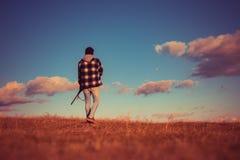 Противозаконный охотясь Poacher в охотнике винтовки леса Silhouetted в красивом заходе солнца Сезон звероловства осени стоковое изображение