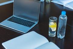 противоокислительн питье и компьтер-книжка на таблице в офисе стоковые изображения