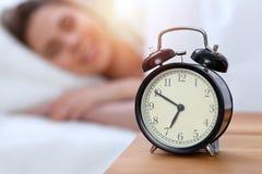 Противоположность будильника красивой молодой женщины спать пока лежащ в кровати удобно и блаженно счастливый поднимающий вверх п стоковые изображения rf
