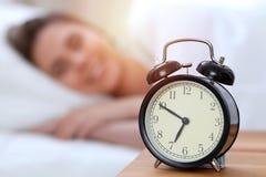 Противоположность будильника красивой молодой женщины спать пока лежащ в кровати удобно и блаженно счастливый поднимающий вверх п стоковое изображение