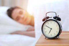 Противоположность будильника красивой молодой женщины спать пока лежащ в кровати удобно и блаженно счастливый поднимающий вверх п стоковая фотография