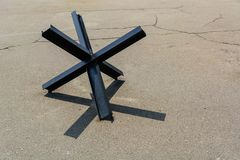 Противотанковое заграждение от рельсов на треснутом старом асфальте против войны расправы стоковое фото rf