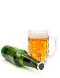 против белизны кружки бутылки пива Стоковые Фото