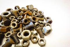 против болтов предпосылки изолированная nuts белизна кучи Стоковые Фотографии RF