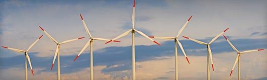 против ветра турбин захода солнца неба Стоковое Фото