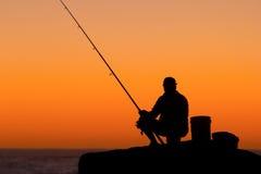 против восхода солнца силуэта рыболова Стоковые Фото