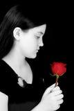 против красивейшей черной девушки смотря красных детенышей розы Стоковое Изображение