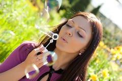 против мыла травы девушки пузыря дуновения предпосылки Стоковое Изображение