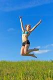 против неба красивейшей голубой девушки скача Стоковая Фотография