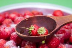 Против предпосылки клубник с сахаром деревянная ложка для варенья Стоковые Фото