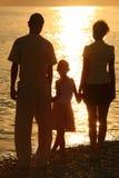 против силуэтов моря семьи глянцуя стоковое фото rf