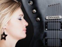 против утеса нот гитары черноты предпосылки пламенистого Гитарист музыканта девушки с электрической гитарой Стоковая Фотография RF