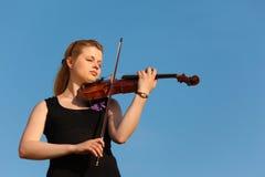 против девушки играет скрипку неба Стоковые Изображения