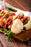 2 протыкальника с мясом и овощем на куске бумаги с травами Стоковые Фотографии RF