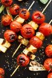 Протыкальники томата сыра и вишни Halloumi на каменной черной предпосылке Стоковые Фото