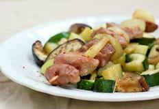 Протыкальник с зажаренным в духовке мясом курицы индюка с луком, цукини и aubergine на белой плите Стоковые Фото