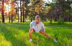 Протягивать белокурую девушку в внешней тренировке Усмехаясь счастливая молодая женщина делая простирания перед бежать Привлекате стоковые изображения