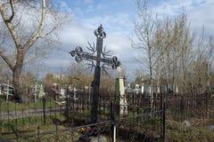 Проутюживьте выкованный крест накрененный среди могил на кладбище 1842 Troitskoye в городе Krasnoyarsk, весной стоковое изображение rf
