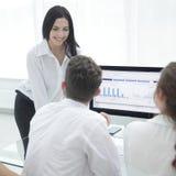 Профессиональная команда дела обсуждая выходящ графики вышед на рынок на рынок на настольном компьютере Стоковые Изображения RF