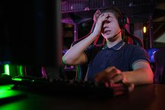 Профессиональная молодая кавказская игра gamer онлайн на его ПК Он осадил из-за терять игру стоковое изображение rf