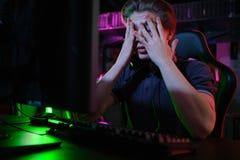 Профессиональная молодая кавказская игра gamer онлайн на его ПК Он осадил из-за терять игру стоковые фото