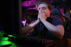 Профессиональная молодая кавказская игра gamer онлайн на его ПК Он осадил из-за терять игру стоковое изображение