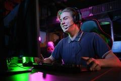 Профессиональная молодая кавказская игра gamer онлайн на его ПК Он осадил из-за терять игру стоковые изображения