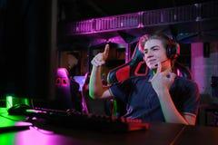 Профессиональная молодая кавказская игра gamer онлайн на его ПК Он осадил из-за терять игру стоковая фотография