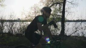 Профессиональная питьевая вода велосипедиста от bidon пока едущ велосипед Река и город на предпосылке r видеоматериал