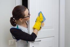 Профессиональная уборка Эконом женщины обтирает дверь с ветошью Стоковое Изображение