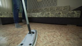 Профессиональная чистка пола с MOP Человек от компании чистки моет пол в живущей комнате сток-видео