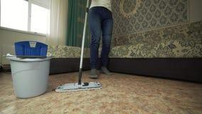 Профессиональная чистка пола с MOP Человек от компании чистки моет пол в живущей комнате акции видеоматериалы