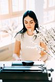 Профессиональное занятие Секретарша в документах белого платья печатая стоковое фото