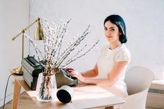 Профессиональное занятие Секретарша в документах белого платья печатая стоковая фотография