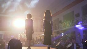 Профессиональные девушки моделей в красивые платья идут вниз с подиума во время представления нового дизайнерского собрания  акции видеоматериалы