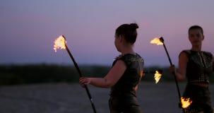 Профессиональные женщины танцоров делают шоу огня и pyrotechnic представление на фестивале с горя сверкная факелами акции видеоматериалы